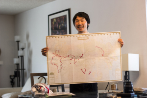"""Ryohei """"Rio"""" Oguchi shows the map with the route he has taken to travel around the world on Nov. 21 during his stop in Bonita. The color red shows the sections he has done biking, the black portions on ground transportation such as bus and train, and the blue portions on ferries or ships. (Photo by Celia Jimenez)"""