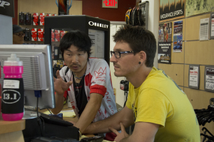 """Daniel Radner, a worker at Pulse bicycle shop in Chula Vista, helps Ryohei """"Rio"""" Oguchi order a new bicycle saddle during Oguchi's stop in San Diego. (Photo by Celia Jimenez)"""