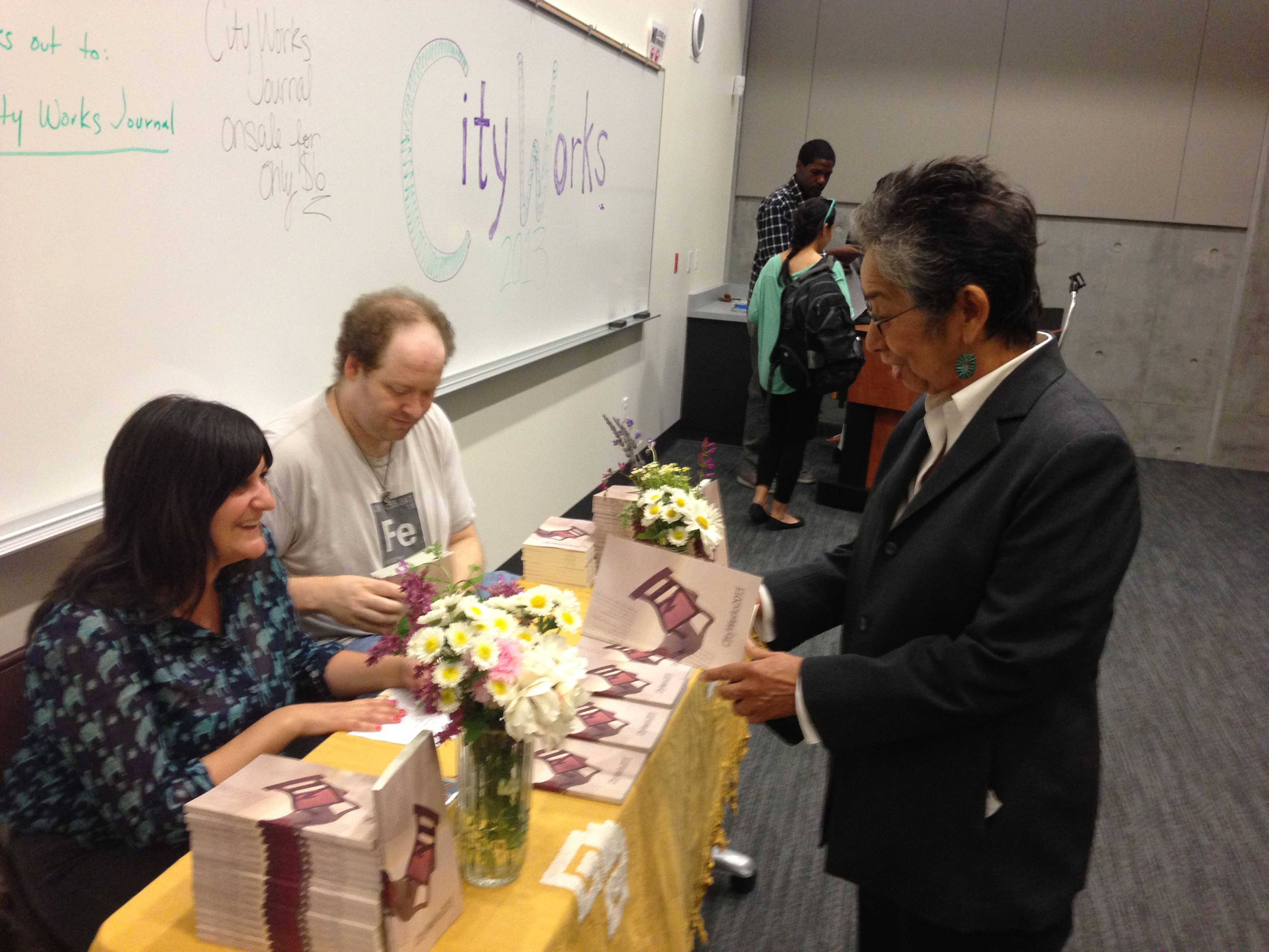 Assistant professor of English, Nadia Mandilawi sells journals for City Works on May 15. by Paul Smoot, City Times