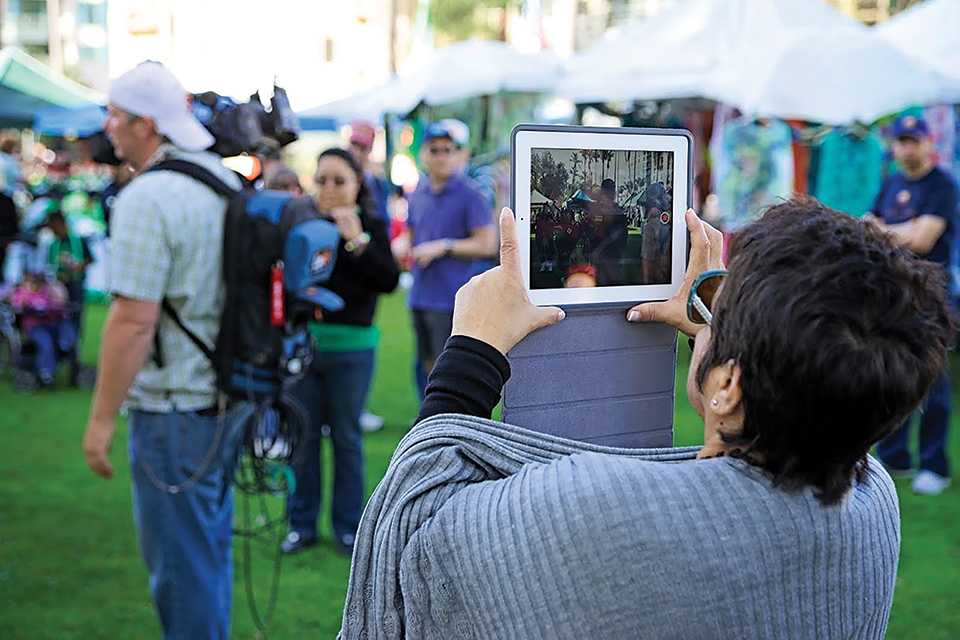 A person recording a St. Patricks Day event on an iPad Photo credit: Troy Orem