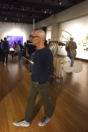 Professor Wayne Hulgin walks through the gallery with his beginning drawing class one night before the opening of the current mixed media exhibition. (Photo by Lupe Diaz)