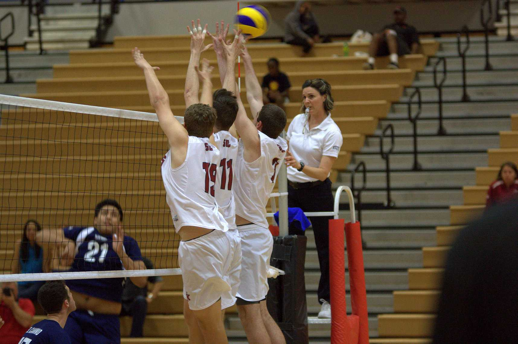 Freshmen (left to right) Jordan Walley, Shane McAdams and Lucas Timm attempt to block the ball but squeezes through their fingertips during the home opener on Feb. 13 against El Camino College at the Harry West Gym. Photo credit: David Pradel