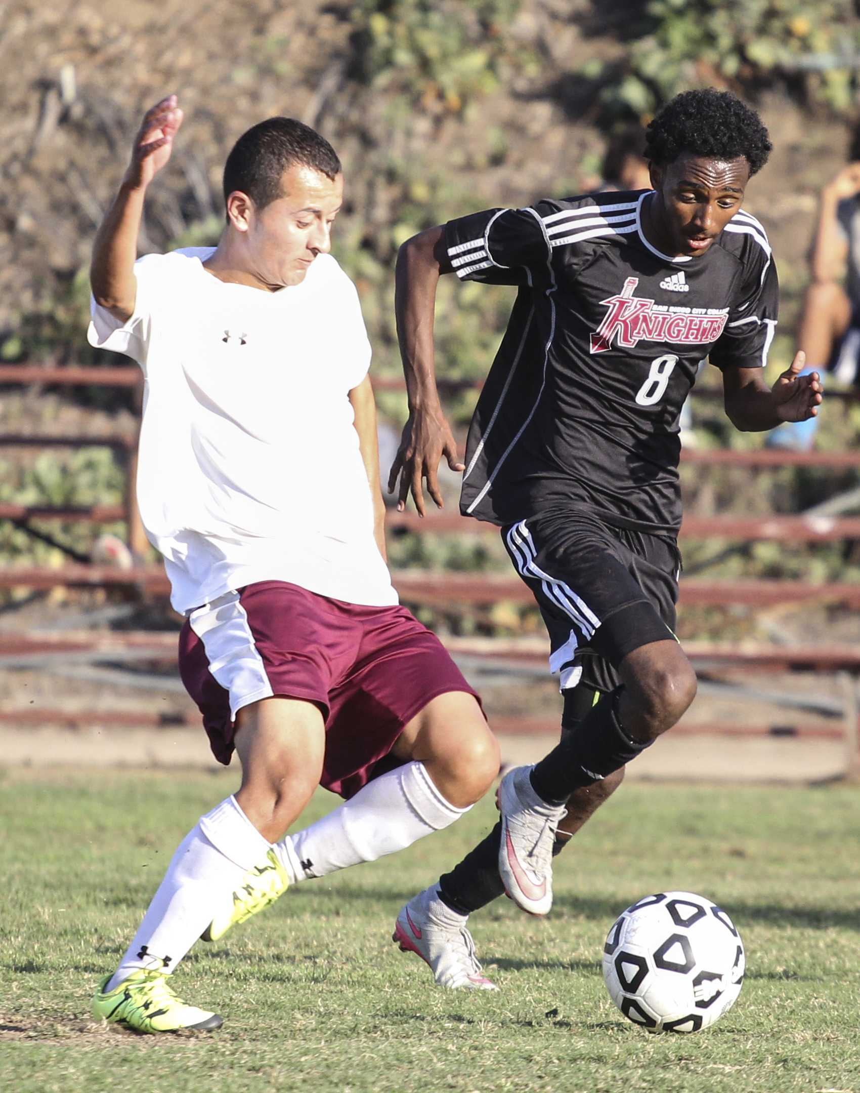 San Diego City College men's soccer midfielder Tadey Anteneh trails Victor Valley Rams freshmen forward Marvin Soriano to stop his advancement to the Knights' goal during their Oct. 23 game on the City College soccer field. Photo credit: Celia Jimenez