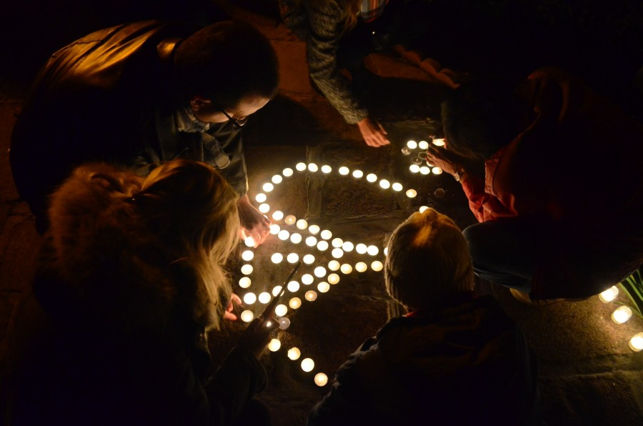 A+group+of+people+make+a+combination+peace+sign+and+Eiffel+Tower+at+the+House+of+France+in+Balboa+Park+on+Nov.+16+during+a+candlelight+vigil+for+the+victims+of+the+attacks+in+Paris+and+Saint-+Denis+that+occurred+on+Nov.+13.+Photo+credit%3A+Richard+Valentin