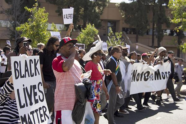 Community residents and faith leaders march Oct. 1 through downtown El Cajon to protest the killing of an unarmed African refugee by a city police officer. Photo by Celia Jimenez / City Times