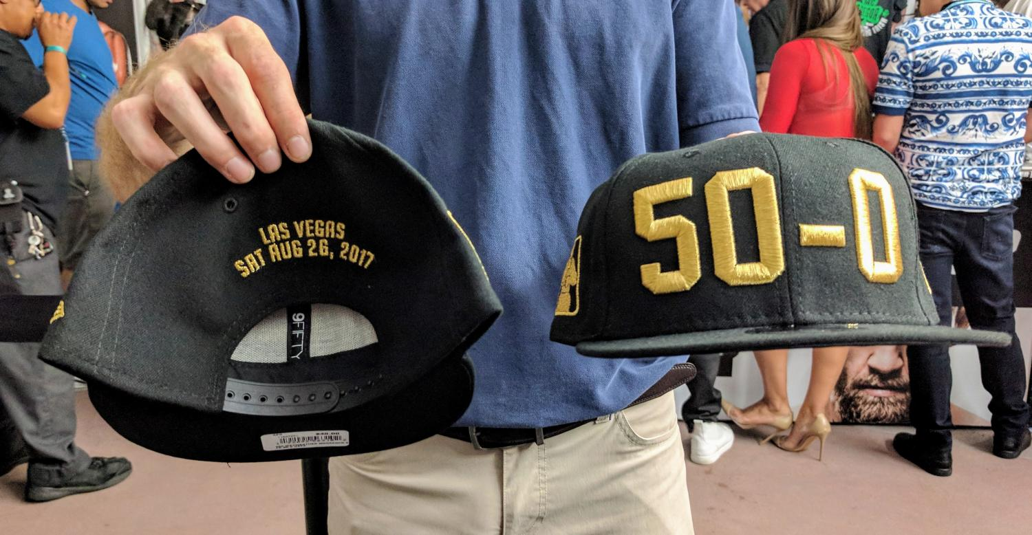 A man holds up the front and back of a baseball cap that mark Floyd Mayweather's record of 50-0