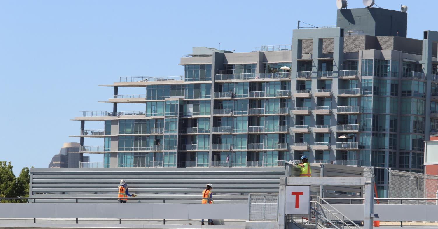 Construction workers applying the final touches on the T building at City College. By David Ahumada.
