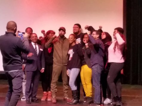 Hip hop artist poses with students, faculty and college president.