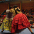 Two Bolivian female wrestlers battle wearing colorful dresses