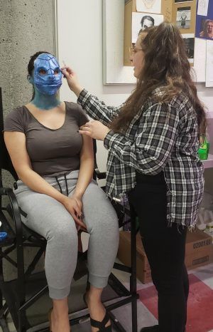 A City FX artist applies makeup to a volunteer.
