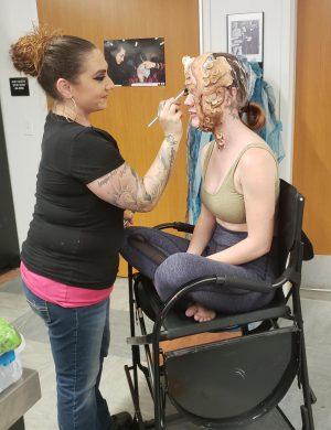 An effects artists applies makeup to a volunt